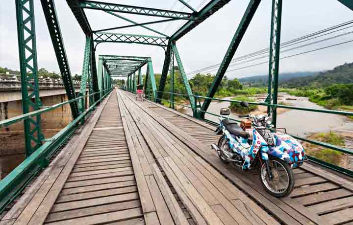 scooter and side car on pai memorial bridge thailand