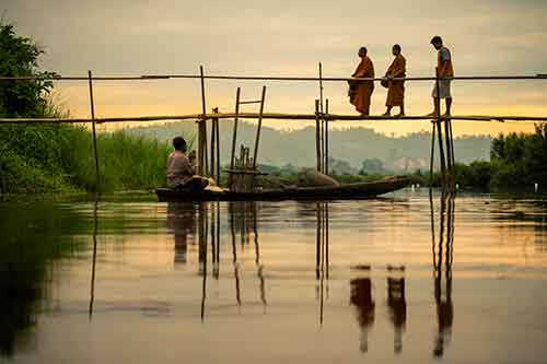 Bhuddist monks walking over a bamboo bridge in Thailand